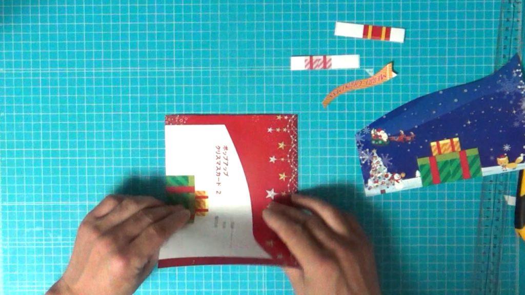 クリスマスカードのベースになる赤い台紙を二つ折りに