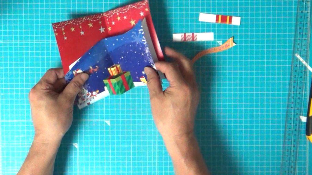 クリスマスカードの赤い台紙に糊で貼ります