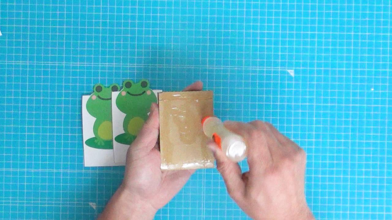 段ボールにのりを塗ってパッチンカエルのイラスト用紙を貼る